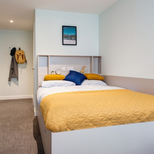 Double bed with yellow throw