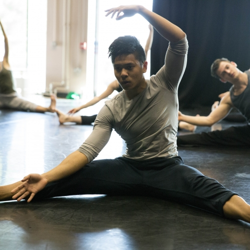 Male dancers stretching.