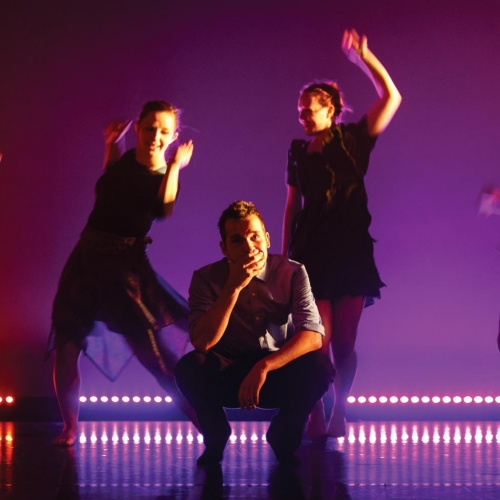 Group of vibrant dancers on stage, purple and red lighting.