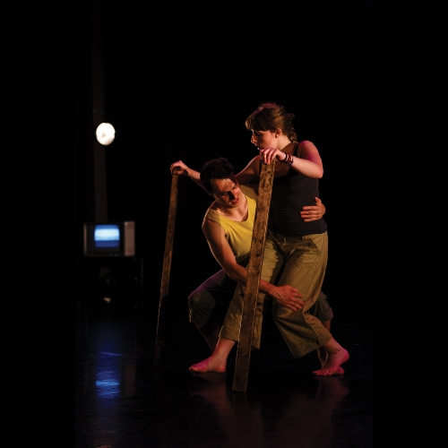 Dancers moving together on stage with planks of wood supporting hands.