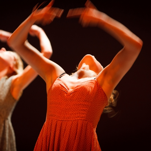 Dancers in dresses throwing hands and heads backwards.