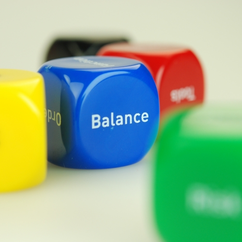 Blue dice with the word 'Balance' and a yellow, red and green dice.