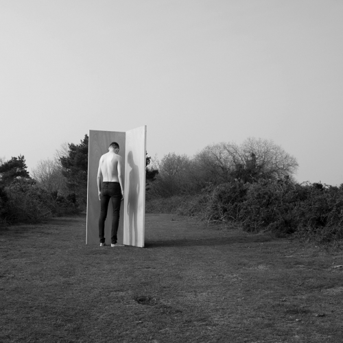 man stood in a field with his face to a wooded panel