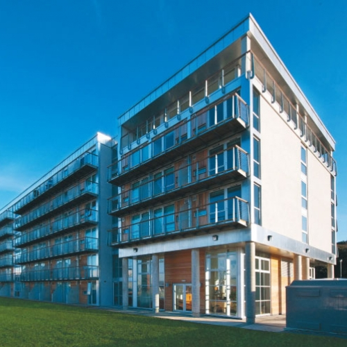 five-storey apartment building with glass balconies, grass and blue sky