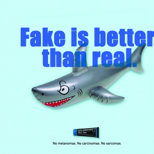 Blow up shark with the text 'Fake is better than real'