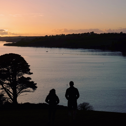 Silhouettes of students looking over the estuary at sunset.