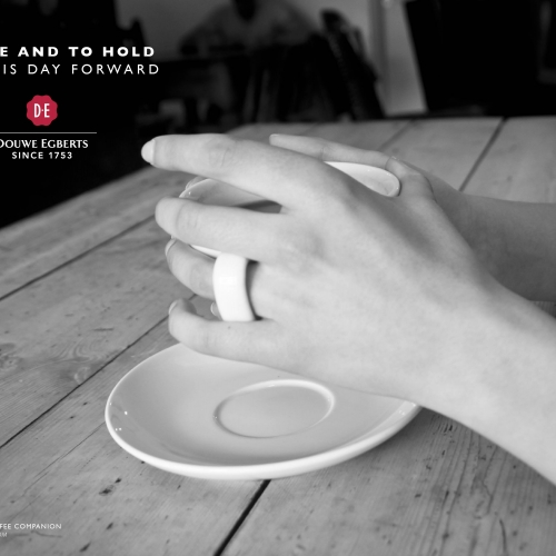 Hands holding a mug of coffee, wedding finger through the the handle.
