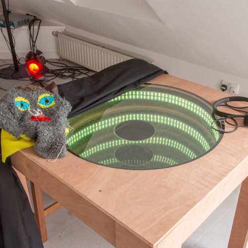Table with circle cut and infinity lights with childlike costume draped over and earphones.