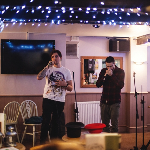 Two students on stage at a poetry slam, blue fairy lights on the ceiling.