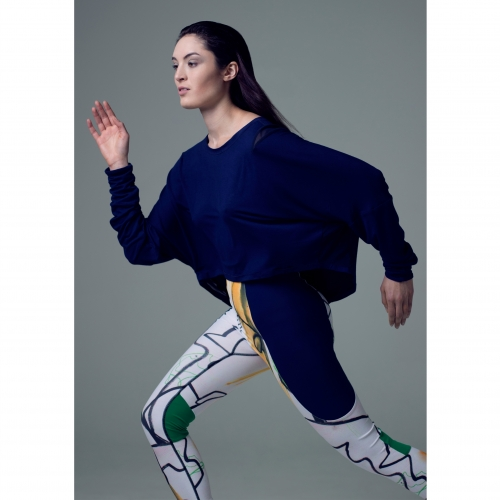 Model in running pose in blue sweater and patterned leggings.