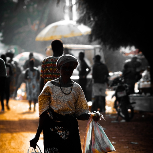 Woman in African dress carrying bags