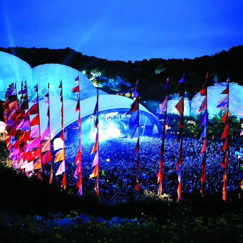 Eden Project biomes lit in blue light with red, pink and purple flags in the foreground.
