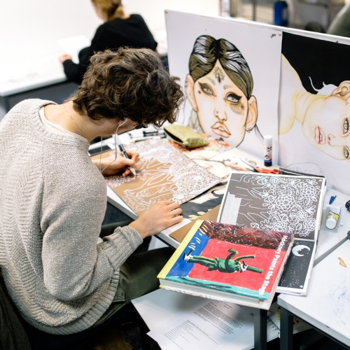 Male student drawing at a desk