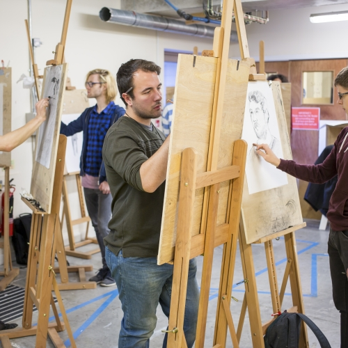 four male students at easels in a life drawing class