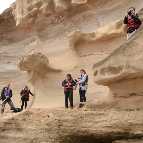 Students with cameras stood on smooth pink coloured rock face.