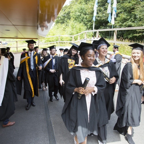 Smiling Falmouth University graduates in gowns and hats walking out of graduation ceremony 2019.