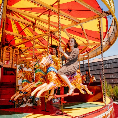Graduates and guests riding carousel at Falmouth University graduation 2019