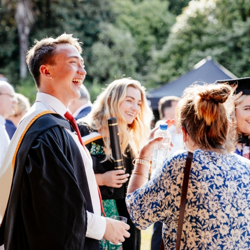 Graduates and guests smiling and talking in the gardens - graduation 2019