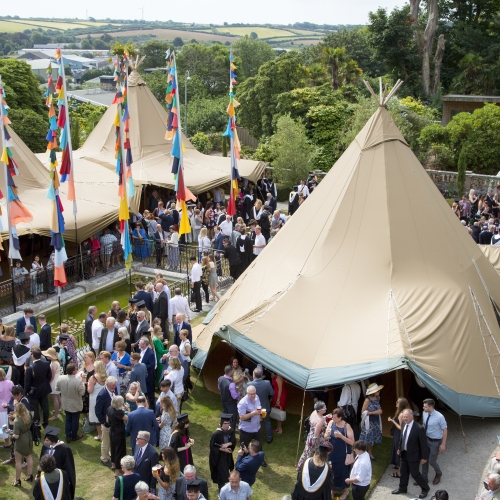 Arial shot of event tents, flags, gardens and guests at Falmouth university graduation 2019
