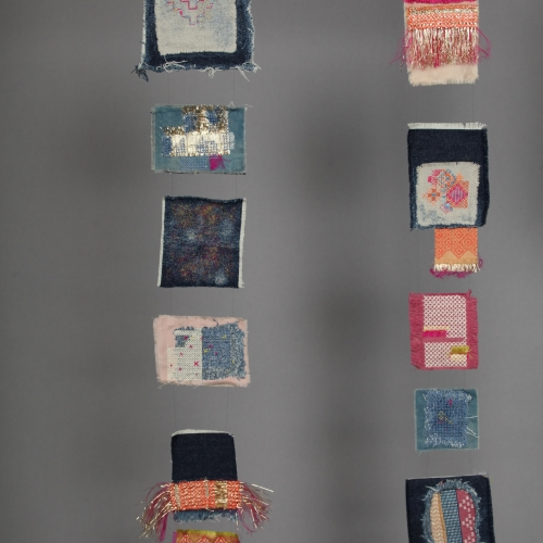 A display of colourful hand stitched embellished rectangles.
