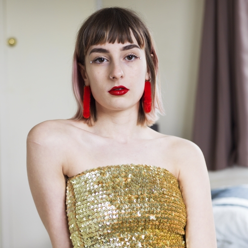 Model with gold sequin top and red tassel earring and red belt sat on a bed.
