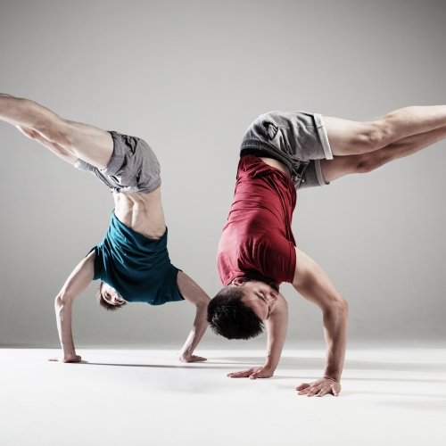 Two dancers doing hand stands and bending at hips so legs are at a right angle mirroring each other.