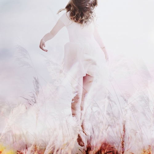 Girl in white dress floating through a field of corn.