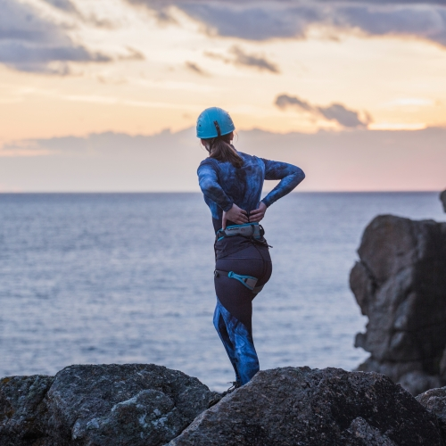 Female in blue helmet and patterned blue sportswear standing on rock and looking out to sea.