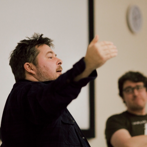 Ben Wheatley gesturing with hand during lecture.