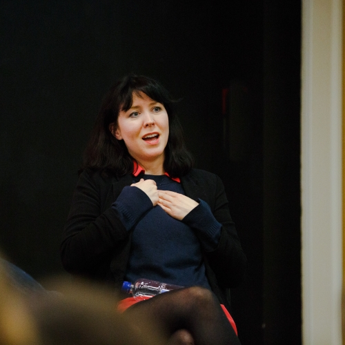 Alice Lowe holding hands to chest on stage in lecture theatre.