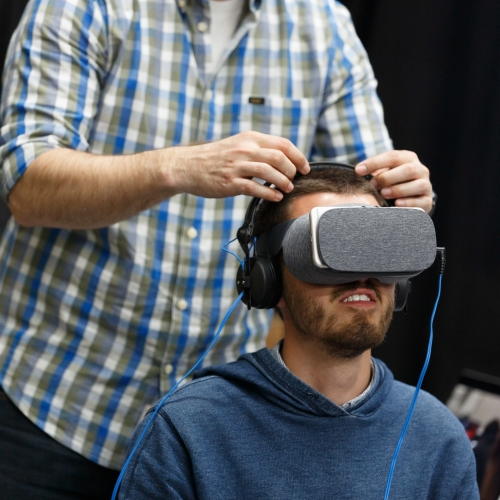 man seated wearing VR headset with another man stood behind him