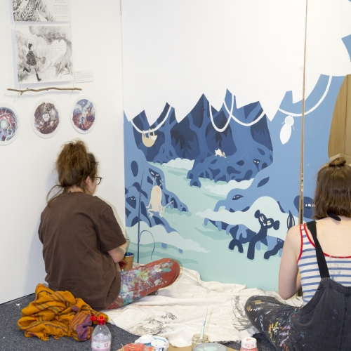 Two female students painting a large canvas