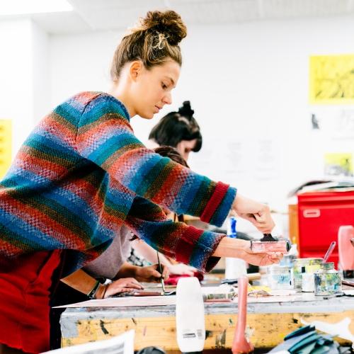 Female student wearing stripy jumper printing in studio