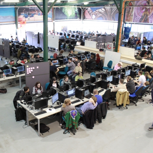 A large warehouse full of students at computers and computer artwork on the walls.