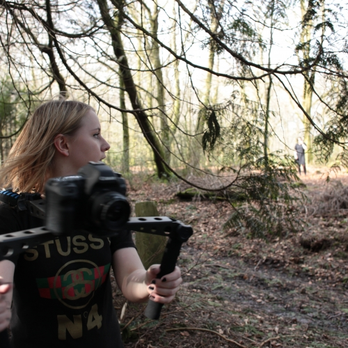 Student in woods with camera on a shoulder mount.