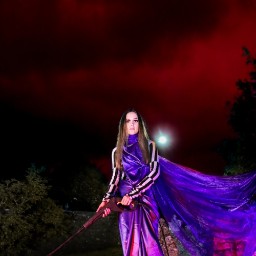 Woman in a long purple dress with a hose