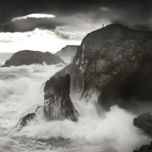 Dramatic grayscale image of sea crashing into cliff with a lone person standing at the top.