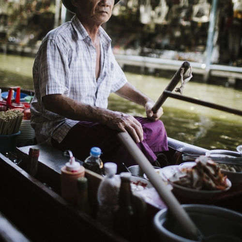 Asian food vendor on boat with food, chopsticks and sauces.
