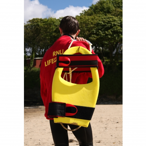 Lifeguard carrying yellow float on back.