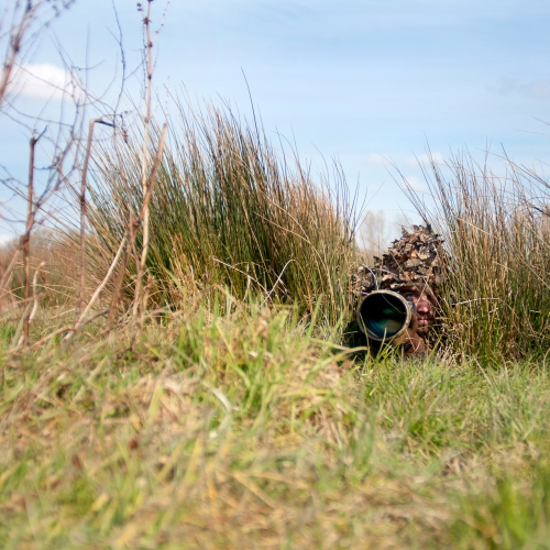 Student lying in grass with leaf camouflage head piece and holding camera.