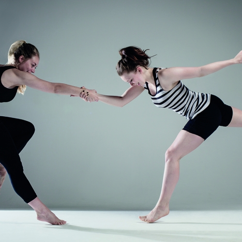 Two dancers in handshake hold and one leg extended and one leg bent