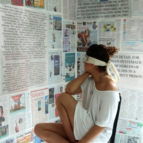 Woman wearing a blindfold while looking at news articles