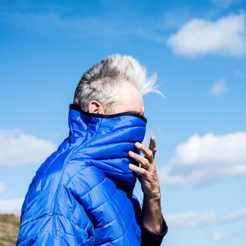 Silver haired man wearing blue padded jacket with high neck up over his face.