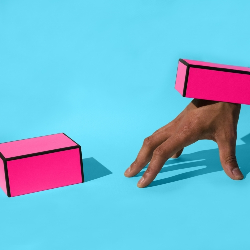 Two pink boxes, one with hand attached and set on a bright blue background.