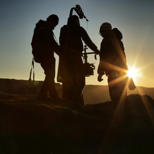 Three silhouettes filming at sunset