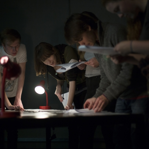 Students problem solving in dark room with lamps