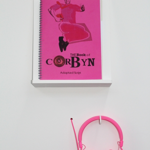 "Pink book called ""Book of Corbyn"" on display with pink headphones."