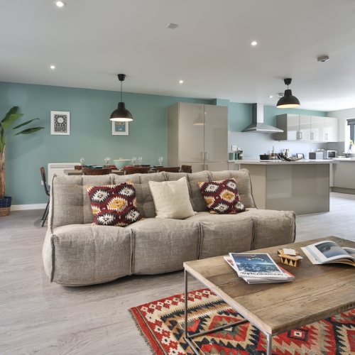 Living room interior with grey sofa and wooden coffee table