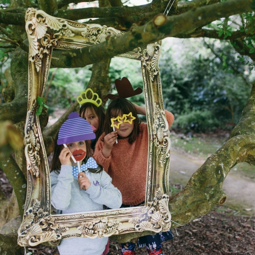 Children posing in woods behind gold gilt picture frame with masks at Little Fay Festival