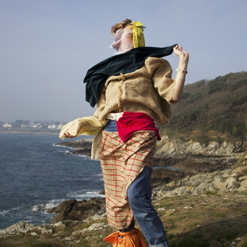 Woman on the cliff top wearing different materials